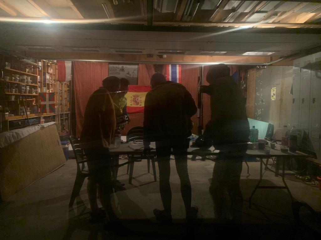 Вот он этот гараж. На столе стоит еда, а за столом лежат матрасы для отдыха